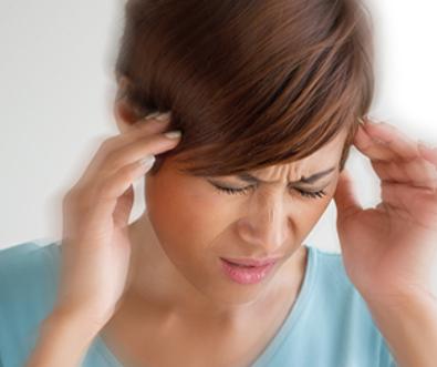 Junge Frau mit Kopfschmerzen, fasst sich an Stirn