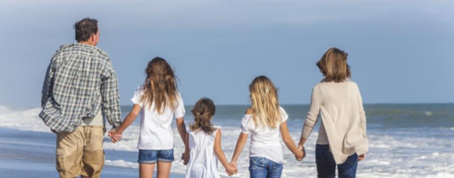 Familie mit drei Kindern am Strand
