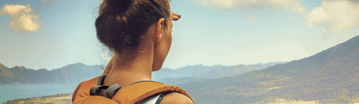 Junge Frau mit Rucksack schaut auf Landschaft