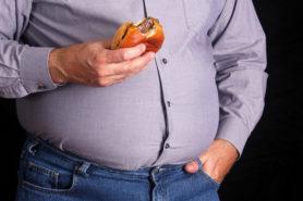 Mann mit dickem Bauch isst Hamburger