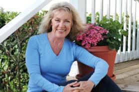 Frau in den 60ern sitzt auf einer Treppe