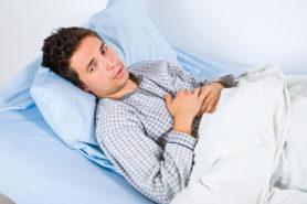 Junger Mann liegt krank im Bett