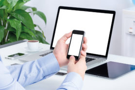 Mann arbeitet mit Smartphone und Laptop