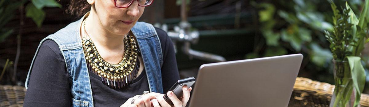 Frau arbeitet mit Smartphone und Computer