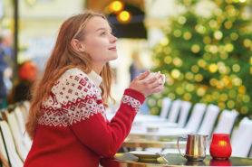 Frau mit rotem Pulli sitzt draussen und trinkt warmen Kaffee