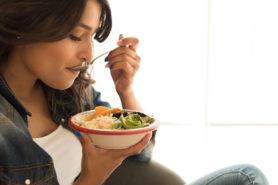Junge Frau isst gesunden Salat