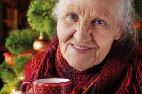 Alte Frau trinkt Tee vor Weihnachtsbaum