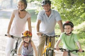 Eltern fahren Farhrrad mit zwei Kindern