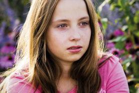 Junge Frau schaut nachdenklich und traurig