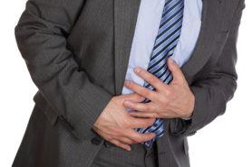 Mann hält sich den Bauch wegen Bauchschmerzen