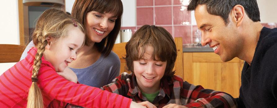 Eltern mit zwei Kindern spielen Domino