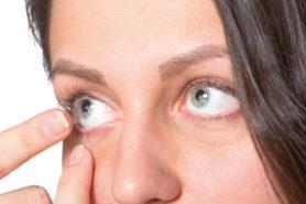 Frau setzt sich Kontaktlinse ein