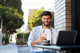 Junger Mann mit Smartphone und Kaffee