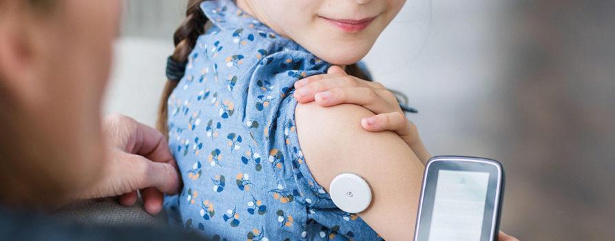 FreestyleLibre Sensor klebt auf Arm eines Mädchens