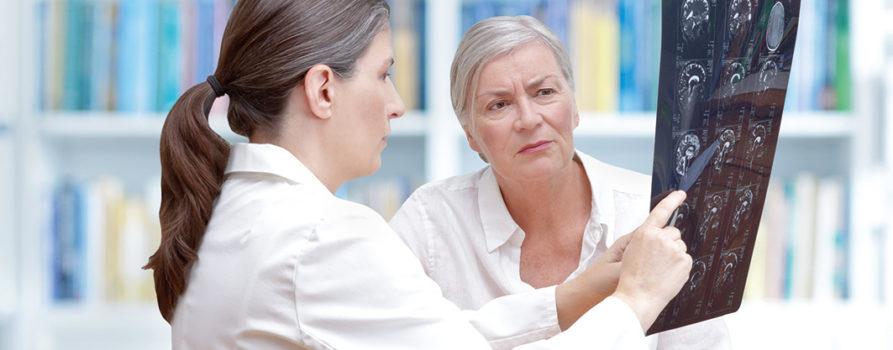 Arzt und Patient beim besprechen von Röntgenbilder des Kopfes