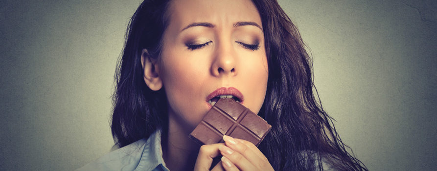 Frau isst mit verzückten Gesichtsausruck Schokolade