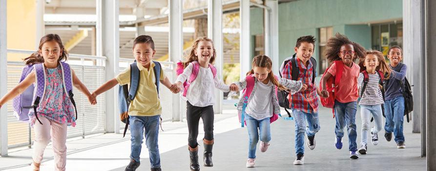 Fröhliche Schulkinder rennen durch Gang