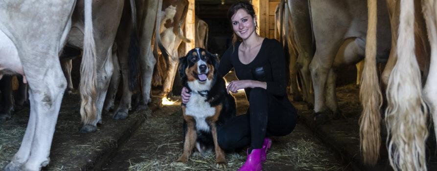 Junge Frau mit Hund im Kuhstall Diabetesbetroffene in Coronazeiten